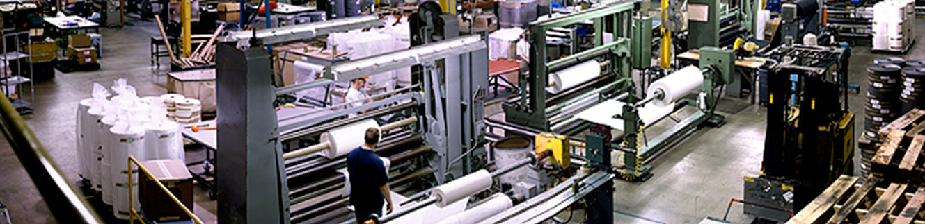 Textile slitting and re-rolling machines cutting fabric in our factory setting.